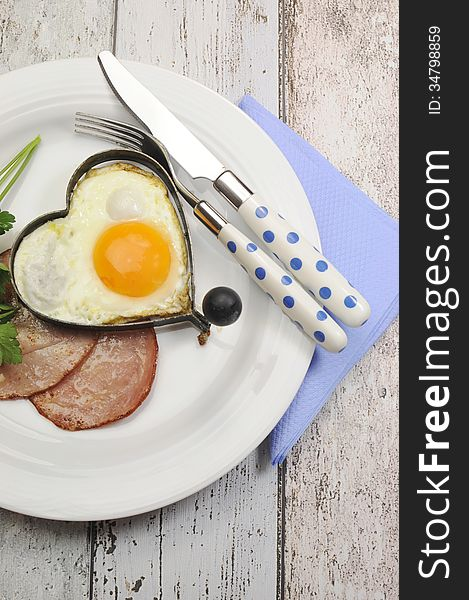 Ham with heart shape egg cooked breakfast - vertical