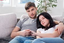 Young Couple Are Sitting Down On A Couch Stock Photos