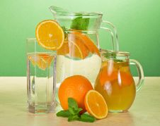 Jugs With Drinks, Glass, Oranges And Spearmint Royalty Free Stock Photography