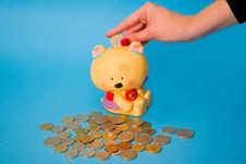 Female Hand Putting Coins In The Piggy Bank Stock Photo