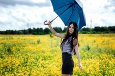 Slim Girl Standing With Blue Umbrella In Yellow Flowers Field Royalty Free Stock Photography