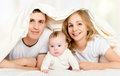 Free Happy Family In Bed Under A Blanket Stock Photography - 35278972
