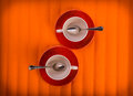 Free Two White Empty Cups With Tea Spoons, On Red Plates Over Orange Color Background, View From Above Stock Photo - 35417370