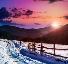 Fence By The Road To Snowy Forest In The Mountains Royalty Free Stock Photo