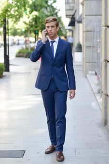 Attractive Young Businessman On The Phone In Urban Background Stock Photography