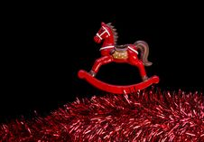 Free Red Color Rocking-Horse Over Claret Garland, Black Background Royalty Free Stock Image - 35544066