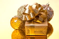 Gift Box And Christmas Balls On Golden Background Stock Photography
