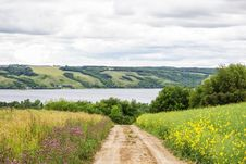 Narrow Dirt Road Leading To A Lake In The Valley Stock Image