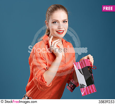 Free Girl In An Orange Shirt And Jeans With Shopping Bag On A Blue Ba Stock Photos - 35839253