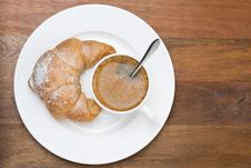 Fresh Croissant And Cup Of Coffee On Plate On Wooden Background Stock Image