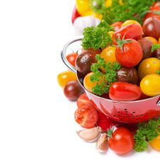Assorted Cherry Tomatoes In A Colander And Fresh Herbs, Isolated Royalty Free Stock Photography