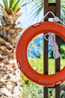 Orange Life Buoy With Rope Hanging Around The Pool Royalty Free Stock Photos