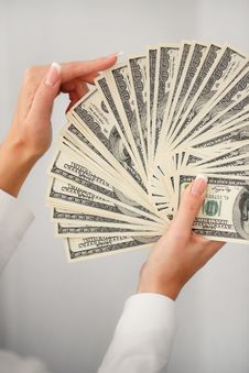 A Young Woman With Dollars In Her Hands, Isolated On White Stock Photo