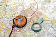 Compass And Handglass On A Map Stock Photography