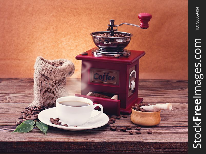 Cup of warm coffee and grinder.