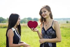 Two Pretty Women In Love With Red Heart In Sunshine Summer Field Royalty Free Stock Images