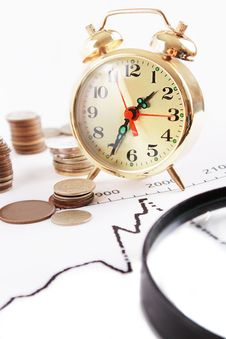 Magnifying Glass, Alarm Clock With Pile Of Coins Stock Photo