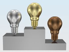 Golden, Silver And Bronze Light Bulbs On Pedestal Royalty Free Stock Images