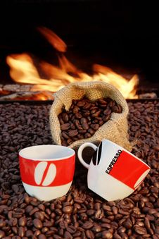Two Cups Of Espresso And Coffee Beans On A Background Of Fire Stock Photos