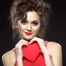 Girl In Red Dress Keeps The Heart. Concept Of Valentine S Day Royalty Free Stock Photography