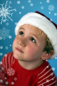 Young Boy In A Santa Hat Looking At Snowflakes Stock Photos
