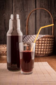 Free Bottle And Glass Of Red Juice On A Wooden Table Royalty Free Stock Photo - 36416455