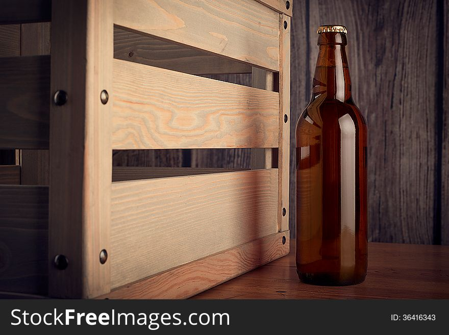 A bottle of beer next to a wooden box