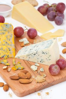 Assorted Cheeses, Grapes And Nuts On A Wooden Board Royalty Free Stock Photos