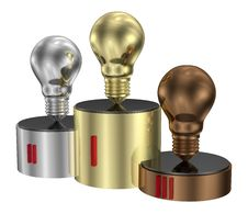 Golden, Silver And Bronze Light Bulbs On Cylindrical Pedestal Of Same Metals Royalty Free Stock Image