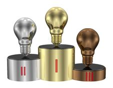 Golden, Silver And Bronze Light Bulbs On Cylindrical Pedestal Of Same Metals. Front View Royalty Free Stock Image