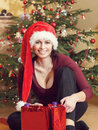 Free Beautiful Middle Age Woman In Santa Hat Sitting Near The Christmas Tree Royalty Free Stock Photos - 36550928