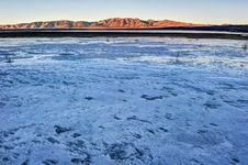 Free Frozen Lake With Grass And Mountains In Background Stock Photography - 36571732