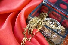 Golden Jewelry On Red Background Royalty Free Stock Image