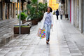 Free Beautiful Woman With Shopping Bags Walking Along A Commercial St Stock Image - 36687071