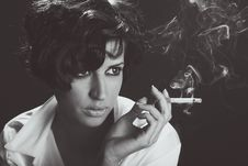 Elegant Brunette Woman Smoking A Cigarette On Black Background Stock Images