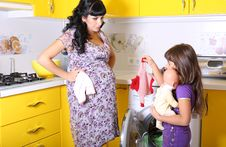 Free Beautiful Pregnant Woman With Her Little  Daughter Beside A Washing Machine Royalty Free Stock Image - 36697076
