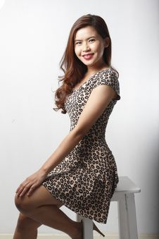 Asian Woman In Dress Sitting On Stool Stock Images