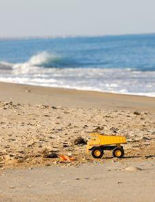 Yellow Toy Truck On Beach Stock Photo