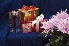 Free Gifts And Candle Behind Flowers Stock Image - 3797041