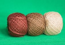 Some Balls Of A Multi-colored Yarn On A Green Background Royalty Free Stock Photo