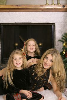 Mother With Twin Daughters By Fireplace Vertical