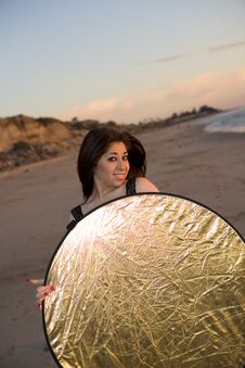 Model Holding A Reflector At The Beach At Sunset Stock Photo