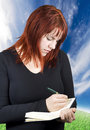 Free Cute Redhead Writing In Her Notebook Or Diary Royalty Free Stock Photos - 3875978