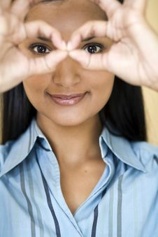 Businesswoman Looking Through Her Fingers Stock Photo