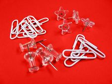 Paper Clips And Push Pins Over Red Background Royalty Free Stock Images