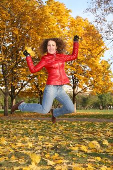 Girl In Red Jacket Jumps In Park Stock Photo