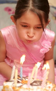 The Girl In A Pink Dress Blows Into Candles Stock Photo