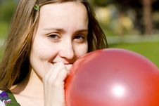 Free Young Woman Inflating Red Balloon Royalty Free Stock Image - 4156576