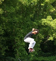 Free Skateboarder Jumping Near Trees Stock Image - 424511
