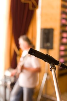 Free Microphone On Tripod With Guitarist On Background Stock Photo - 4271940